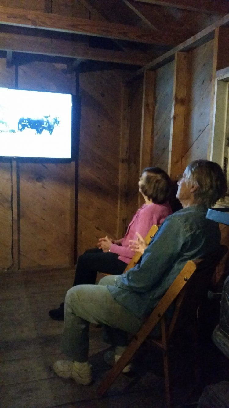 Visitors watch a short film about cowboys and ranching.